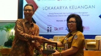 Anggota Dewan Komisioner OJK Tirta Segara saat menerima cendramata dari Kepala Dinas Perindustrian dan Perdagangan (Disperindag) Sulawesi Utara Yenny Karouw