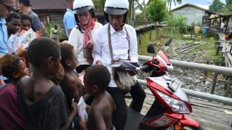 Joko Widodo sebagai presiden RI didampingi istrinya saat kunjungan ke suku Asmat Papua membagi-bagi buku kepada anak-anak disana. (Foto: net)